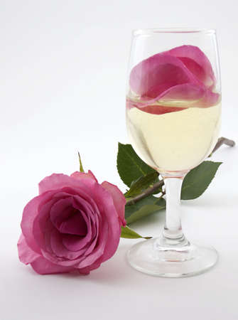 Photo of a glass of champagne with rose petals in it and a rose laying next to it