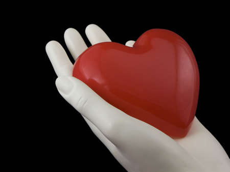 Photo of a hand holding a heart isolated on black Stock Photo - 699599