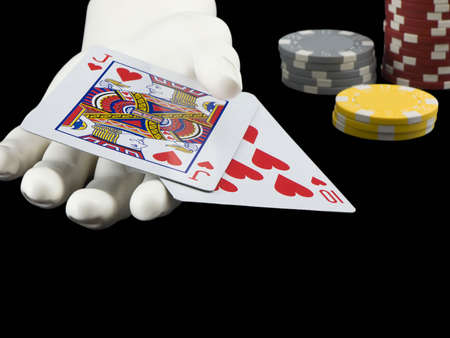 Photo of a hand holding a winning hand in blackjack with poker chips in the background isolated on black Stock Photo - 706201