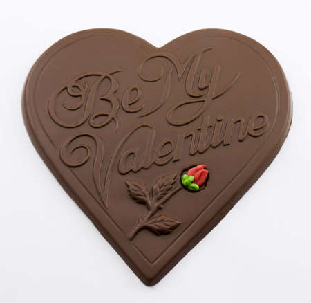 Photo of a chocolate shaped heart with the words, be my valentine, on it and a rose Stok Fotoğraf