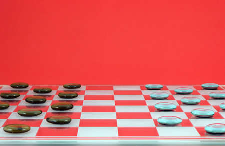 Checkers board with pieces on a red background Stock Photo - 742145