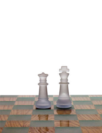 Photo of a king and queen chess pieces on a chess board isolated on white