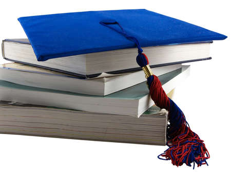 Photo of several textbooks with a graduation cap on top, isolated on white
