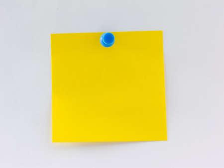 壁に固定されている空白の黄色のメモ