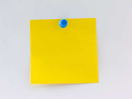 Blank yellow note pinned to a wall