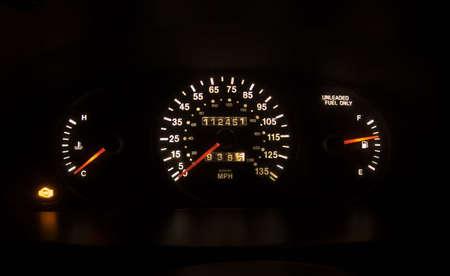 Foto van een verlicht snelheidsmeter met controle van de motor licht op