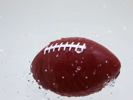 Football in motion coming out of water