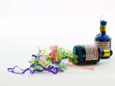 Two party poppers with confetti on a white background Archivio Fotografico