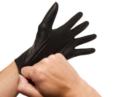 Hand pulling on black latex glove, isolated on white