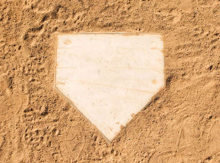 Home plate on a baseball field surrounded by dirt