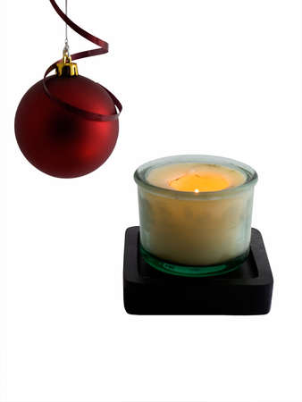 Christmas ornament and lit candle isolated on white