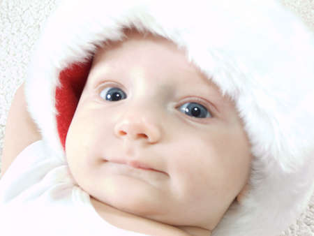 Young baby boy wearing santa hat and smiling