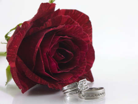 Two diamond wedding rings set in front of a red rose Stock Photo