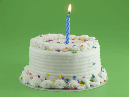 White frosted cake with a lit candle in it