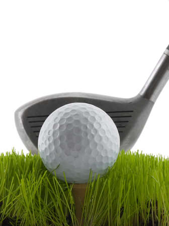 Golf ball on a tee in grass about to be struck by a golf club