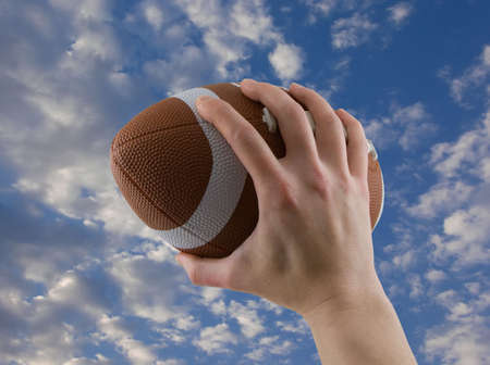Hand passing or catching a football with cloudy sky background