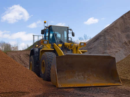 Front-end loader surrounded by hills of dirt and stone