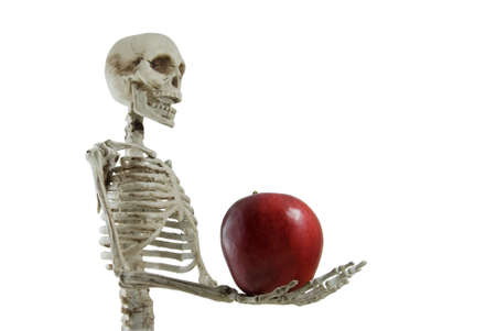 to tempt: Skeleton holding an apple in his hand, isolated on white