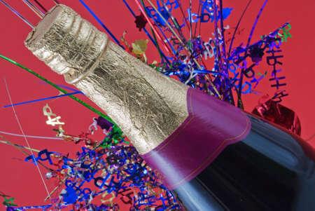 Champagne fles met gekleurde confetti achter  Stockfoto