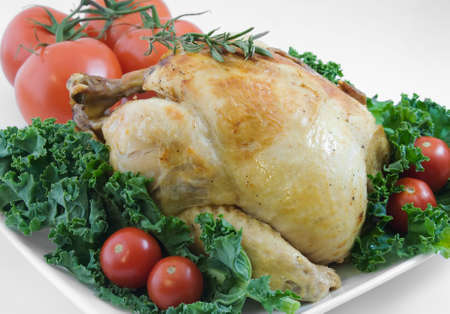 Whole roasted chicken garnished with kale, cherry tomatoes, and rosemary Banco de Imagens