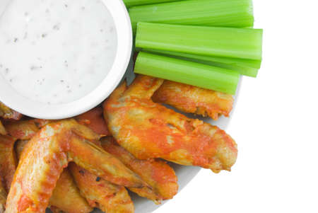 Plate of buffalo wings, celery and blue cheese dressing isolated on white photo