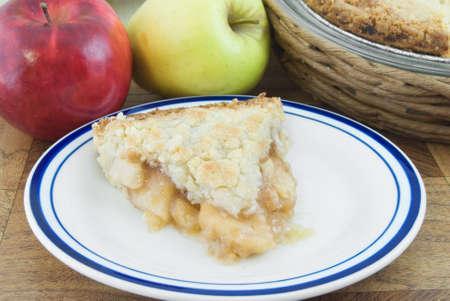 Stuk van de Nederlandse appeltaart op plaat met appels en taart achter Stockfoto