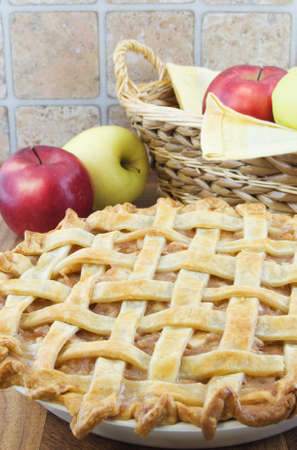 Baked apple lattice pie with wicker basket and apples behind Stock Photo
