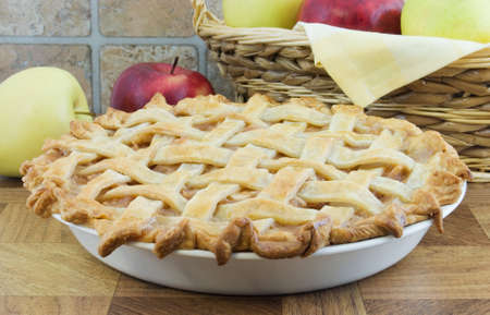 Lattice apple pie with wicker basket and apples behind