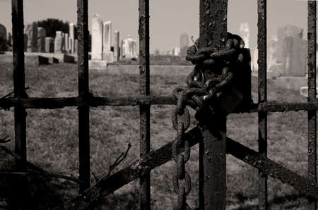 Chained cemetery gate in sepia tones Stock Photo