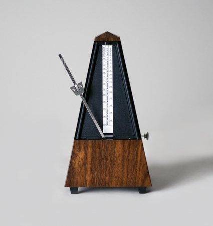 Metronome in action, closeup, isolated and on a plain background