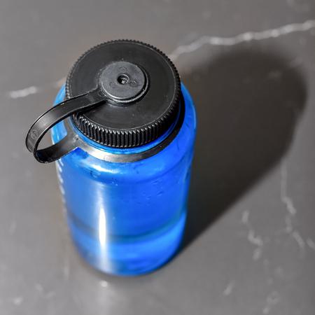 Blue water bottle with screw-on lid in light Standard-Bild