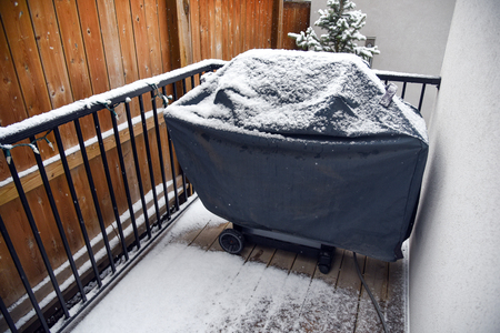 Barbecue covered in snow on deck Standard-Bild