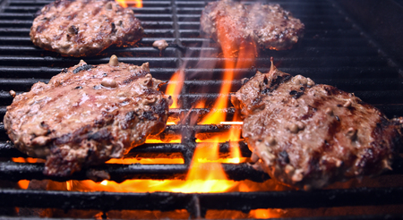 Grilling burgers on a barbecue with flames