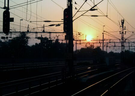 Railway tracks and cables at sunset Standard-Bild