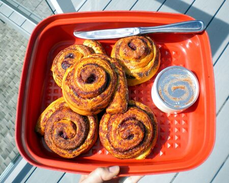 Cinnamon buns in an orange container