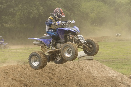 Young boy at quad motorbike race jumps