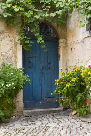 backstreet: Old blue door and flowers in pots  City of Rovinj, Croatia, Europe