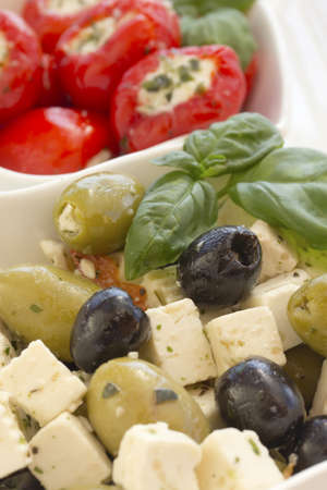 Salad of black, green olives with pieces of cheese  Garnished with basil leaves  The white bowl  Spicy round red peppers stuffed with cheese in the background