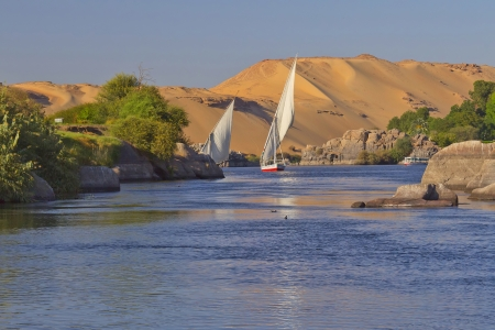 east river: Typical sailing on the Nile  In the background sand hills and blue sky   near Aswan, Egypt   Vertically