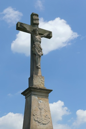 Statue of Jesus Christ on a cross  Blue sky with clouds in the background  photo