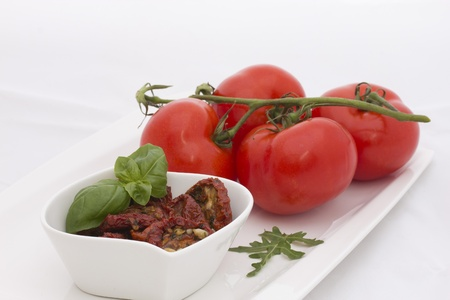 Dried tomatoes with basil leaf in a bowl  In the background are shrub tomatoes  Macro view  photo