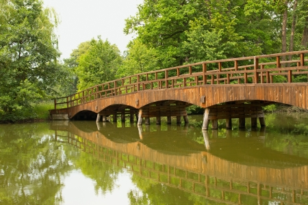 Wooden bridge over a quiet river, lined with green trees  Lednice, Czech Republic  photo