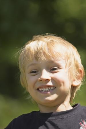 gladden: Close up of a blond boy head having fun Outdoor