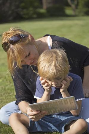 Hijo con pantalla táctil de Tablet PC con su madre El muchacho sostiene su cabeza en sus manos Foto de archivo