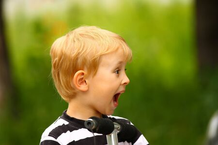 exaggerate: Surprised blond boy  green background