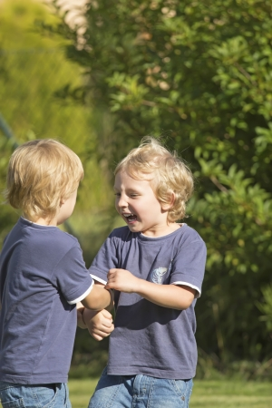 gladden: View of two blonde boys who talk in the garden  One laughs