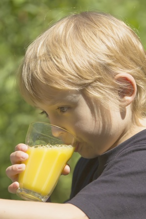 The blond boy is drinking a glass of juice  photo