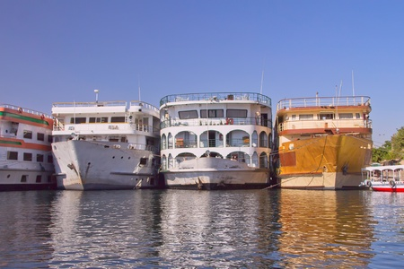 Boats  hotels  anchored in the harbor on the banks of the Nile  Passengers pass through other ships to shore   Luxor, Egypt