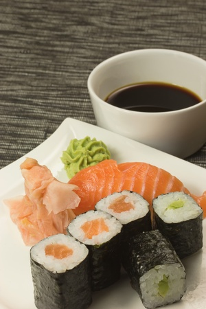 Maki rolls, nigiri sushi and ginger with wasabi on a plate  In the background is a bowl with soy sauce  Vertically   photo