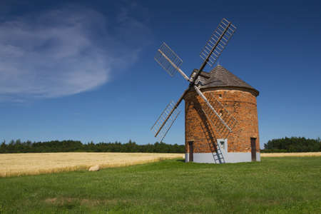 Brick windmill in a field of corn  Blue sky in the background   Chvalkovice, Czech Republic  photo